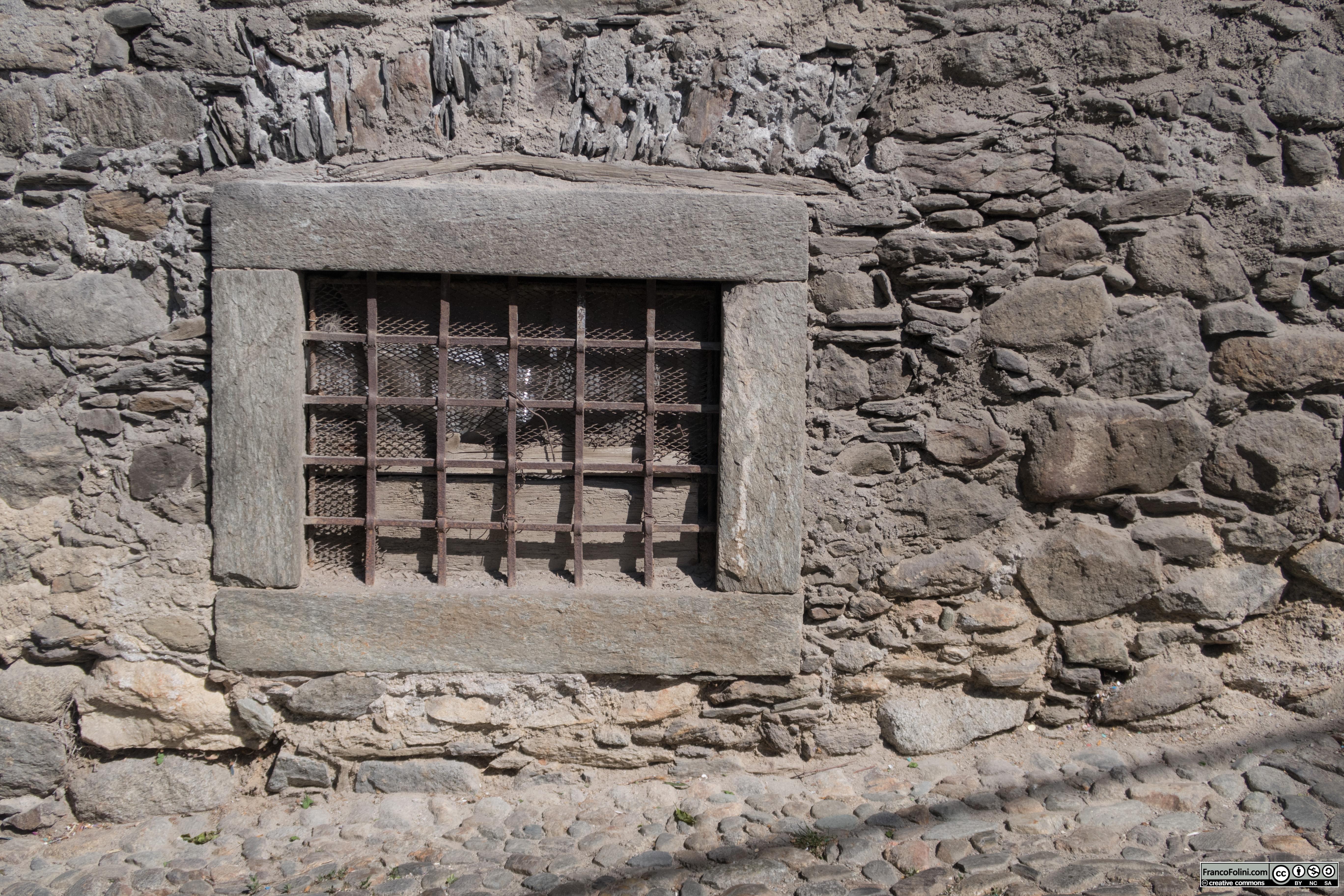 Antico finestruolo medievale con grata, Ponte in Valtellina