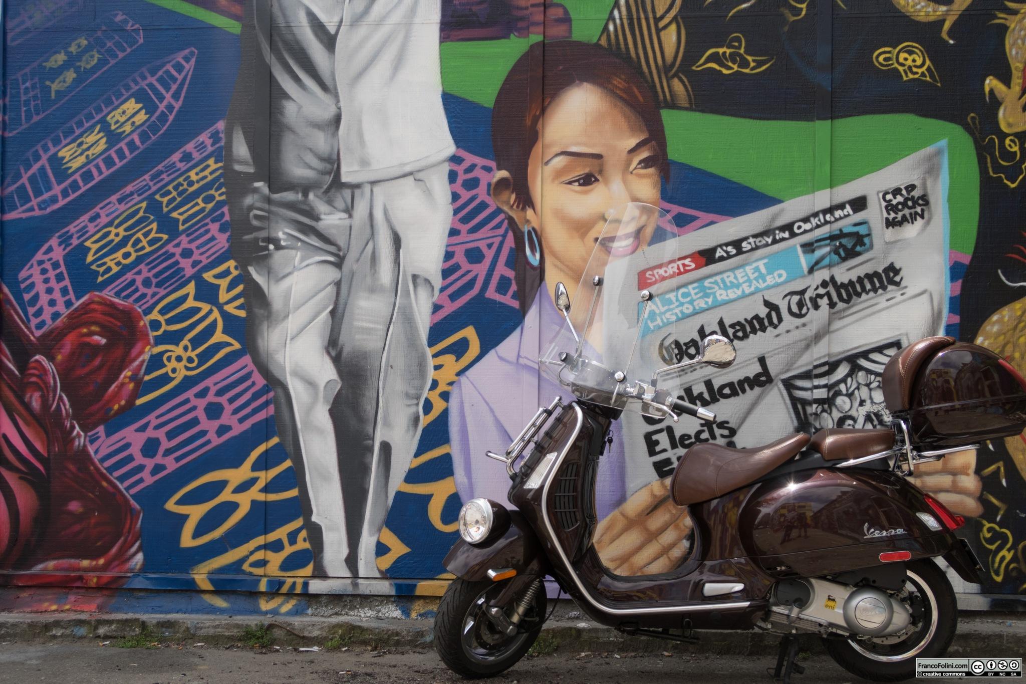 Vespa davanti a murale nel centro di Oakland