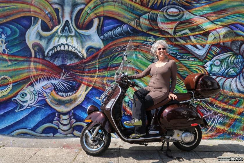 """La muralista messicana Juana Alicia a cavallo della mia Vespa davanti al suo murale """"The Spill"""""""