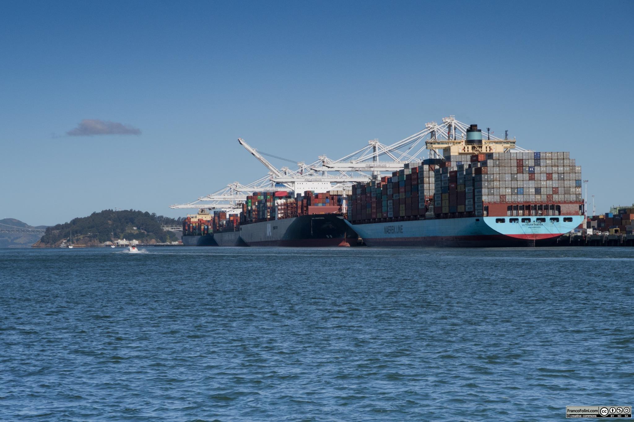 L'affollato porto di Oakland visto dall'isola di Alameda. Si notano le immancabili navi porta-container che vengono caricate e scaricate dalle immense gru bianche visibili sullo sfondo. Il porto di Oakland è il quinto porto più importante degli Stati Uniti