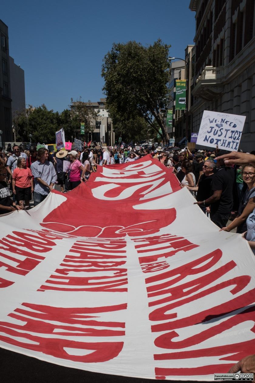 """Lo striscione di protesta comincia a muoversi verso le zone """"calde"""" della manifestazione"""