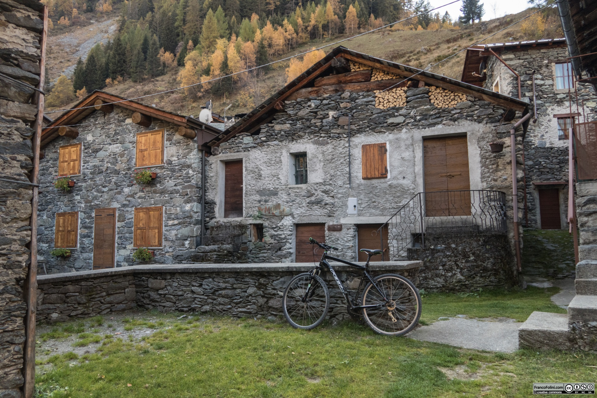 La stradina che rapidamente sale da Vedello verso l'abitato di Ambria in questo tratto passa sotto le condotte forzate che scendono dalla valle e lago di Zappello.