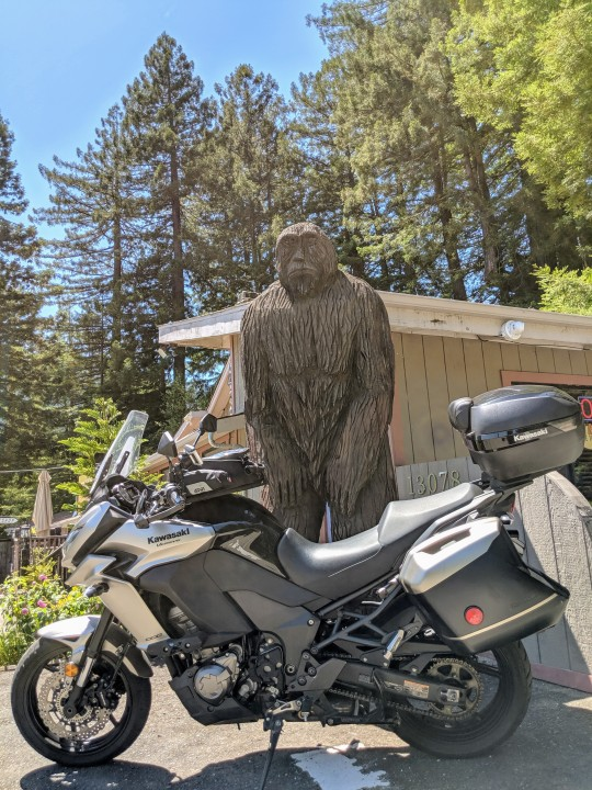 Kawasaki Versys 1000 LT in front of a huge Big Foot wooden sculpture. Myers Flats, California