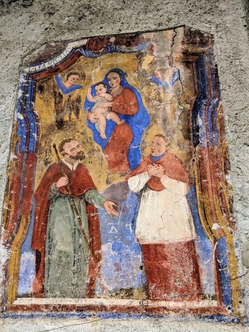 """Affresco votivo. Due santi, quello a destra dovrebbe essere San Luigi Gonzaga, in adorazione della vergine Maria con il bambin Gesù. Iscrizione """"La Famiglia Cantoni"""". Arigna contrada Fontaniva, provincia di Sondrio."""