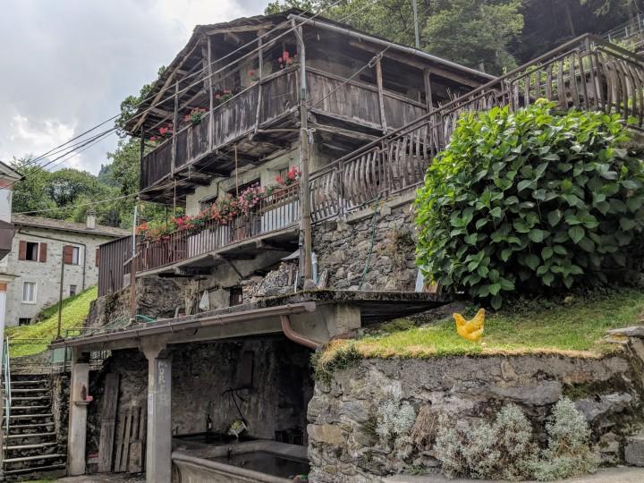 Tradizionale abitazione alpina con fontana e lavatoio. Arigna, contrada Fontaniva, provincia di Sondrio.