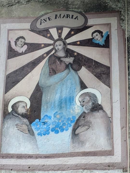 """Affresco votivo. Due santi in adorazione della vergine Maria. Iscrizione: """"Ave Maria, Restauro Agosto 1969, Elena Morelli"""". Il restauro sembra aver danneggiato l'affresco originale e aver reso irriconoscibili i due santi."""