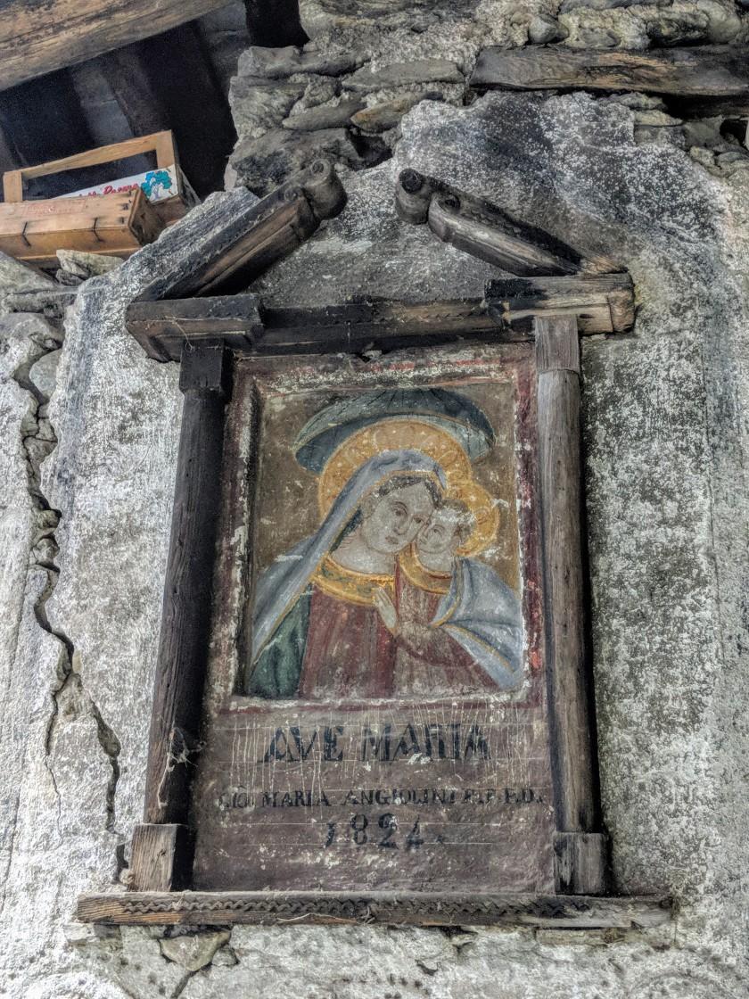 """Affresco votivo. Vergine Maria col bambin Gesù. Iscrizione: """"Ave Maria, Maria Angiolini F.F.P.D. 1824"""". Arigna (Fontaniva), provincia di Sondrio."""