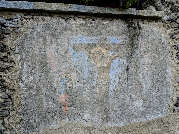 Affresco votivo scolorito dal tempo. Crocifissione con vergine in adorazione.