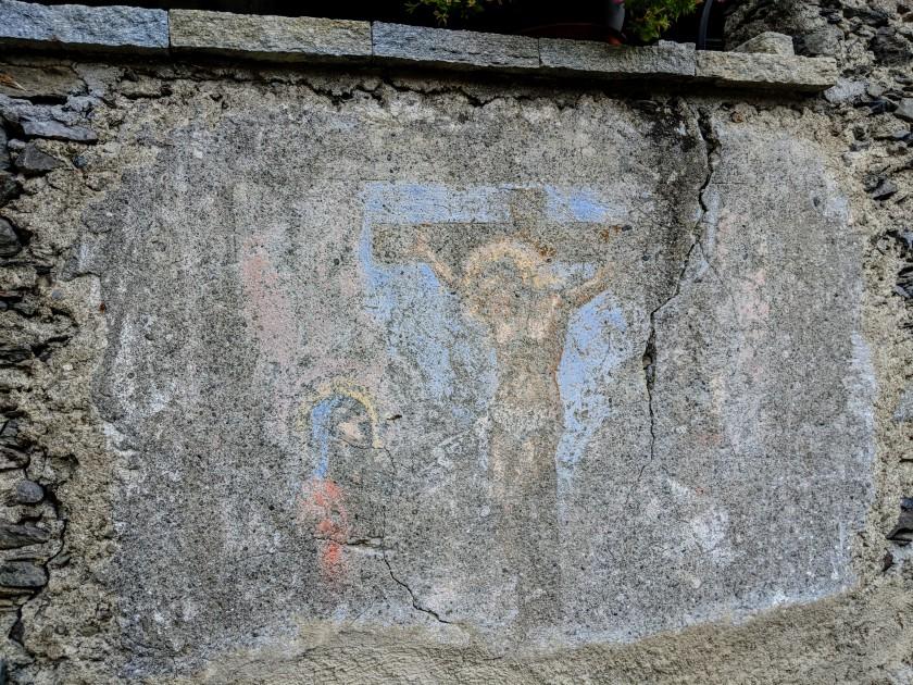 Affresco votivo scolorito dal tempo. Crocifissione. Arigna (Fontaniva), provincia di Sondrio.