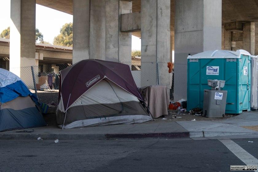 Accampamento di homeless (senzatetto) sotto i cavalcavia dell'autostrada 280 a Oakland, California. Sulla destra si vede un blocco in plastica grigia: si tratta di un distributore di acqua potabile fornito dalla città di Oakland per alleviare le condizione disperate degli abitanti di questo accampamento illegale.