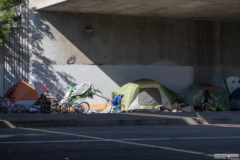 Alcune tende dell'accampamento di homeless (senzatetto) sotto i cavalcavia dell'autostrada 280 a Oakland, California. Molte di queste tende sono posizionate in situazioni di oggettivo pericolo e pongono gli homeless a costante contatto con i gas di scarico del traffico. È successo recentemente che un auto sbandando andasse a investire una di queste tende.  Fortunatamente al momento dell'incidente la tenda era vuota.